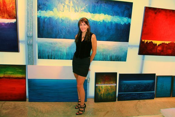 Leanne Venier in her Austin Gallery with her international award-winning paintings that she created while in Flow State