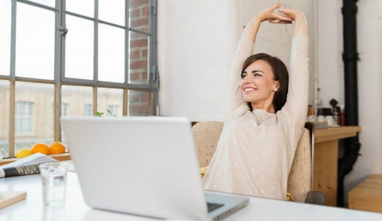 Happy woman at work next to a window on computer stretching