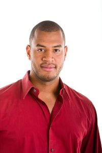 An attractive, young, athletic looking young black man in a red casual shirt isolated on white