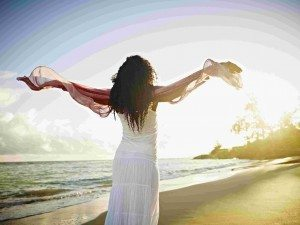 Woman with arms outstretched towards sun